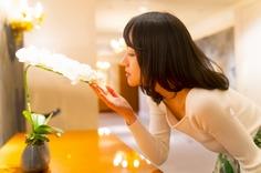 ミニ胡蝶蘭のニオイをかぐ女性